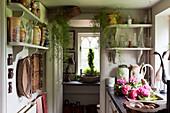 Vasensammlung auf Wandregalen in kleiner Landhausküche