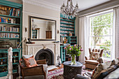 Turquoise bookcases flanking fireplace in English-style living room