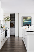 Glance into bright contemporary kitchen with white kitchen unit and kitchen island