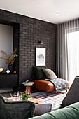 Lederhocker vor schwarzer Backsteinwand im Wohnzimmer