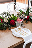 Arrangement of protea and olive branches on a laid table