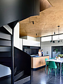 Black spiral staircase in architect's house with open kitchen