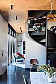 Spiral staircase in the open living room in shades of gray in the architect's house