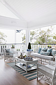 White wicker furniture with light blue decorative pillows on a covered veranda