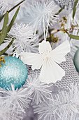Paper angel next to ice blue Christmas ball in the fir tree