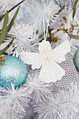 Papierengel neben eisblauer Weihnachtskugel im Tannenbaum