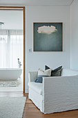 Sitting area with armchair in front of passage to modern white bathroom