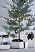 Elegant verpackte Geschenke vor dem Weihnachtsbaum