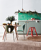 Round table with chairs and green tiles above base cabinet in kitchen decorated for Christmas