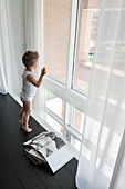 Little boy standing on black floor next to window