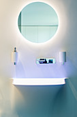 Round mirror with indirect lighting in designer bathroom
