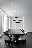 Elegant, black dining table with designer chairs in minimalist interior
