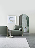 Reduced furnished living room in gray and white with sofa and arched passage