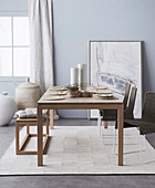Living room in muted natural tones with a dining table, floor vases and an abstract mural