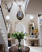 Foyer decorated with antlers and ornate mirrors above console tables