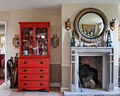 Red-painted mahogany dresser next to round mirror above fireplace