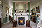 Antique mahogany turf buckets holding firewood in front of fireplace below large mirror