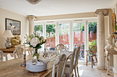 Dining table and terrace doors framed by columns in Neoclassical living room