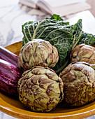 Fresh artichokes, aubergines and Savoy cabbage in ceramic bowl