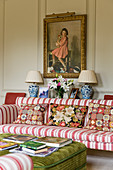 Antique painting above striped sofa with tapestry scatter cushions in English manor house