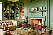 Open fireplace in library with green wooden panelling in renovated English manor house
