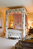 Four-poster bed with chintz curtains in olive-green bedroom in English manor house