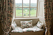 Floral cushions on window seat with curtains