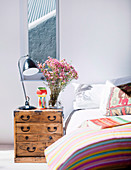 Antique, Asian chest of drawers as a bedside table next to a double bed in a bright bedroom