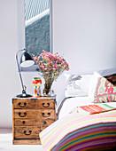 Antike, asiatische Kommode als Nachttisch neben Doppelbett in hellem Schlafzimmer