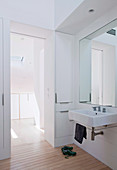 Weißes Badezimmer mit Einbauschrank, Spiegel und Waschbecken