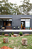 Modern house made of gray corrugated iron with terrace and garden