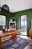 Plastic chairs on wooden table in dining room with green walls