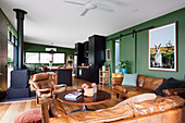 Open living room with green walls and leather furniture