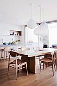 Designerstühle am modernen Holztisch in der Wohnküche