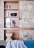 Built-in shelf in a natural stone wall in the bedroom