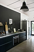 Kitchen counter with black cabinet against black wall