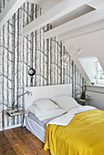 Bed under sloping ceiling and against wall with forest-motif wallpaper