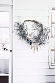 Wreath of found objects from nature on the house wall