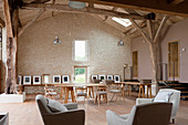 Gallery of artworks and seating area in renovated barn converted into workshop studio