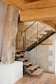 Staircase leading to gallery in converted, renovated barn