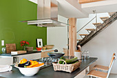 Island counter in open-plan kitchen below gallery in converted barn