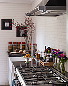 Gas cooker in kitchen with white brick wall