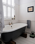 Free-standing bathtub supported by two wooden blocks in classic bathroom