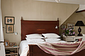 Pillows stacked on wooden bed with quilt