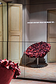 Red designer armchair reflected in mirrored cabinet with illuminated lettering