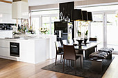 Black, modern dining set in front of white, open-plan kitchen