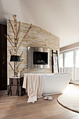 Free-standing bathtub in front of fireplace in stone wall