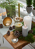 Festive arrangement of candles, pine cones and moss on table