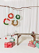 Christmas wreaths handmade from fabric remnants, wooden bench and wrapped Christmas gifts