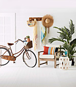Armchair, side table, indoor palm tree and bicycle